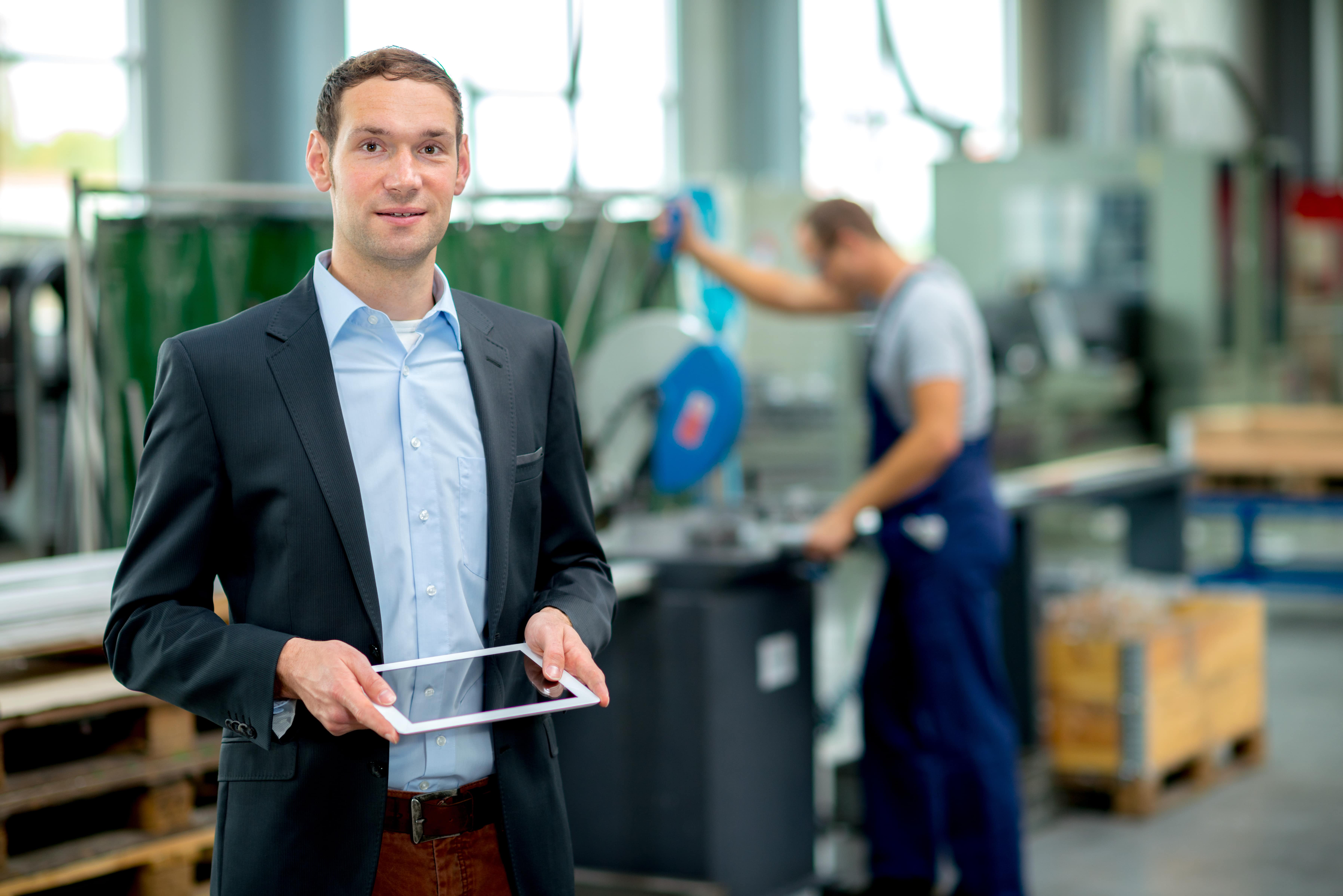 A man with a suit is holding a tablet in na industrial plant, looking straight to the camera. He seems friendly and positive. At the background, there is a blurred man working.
