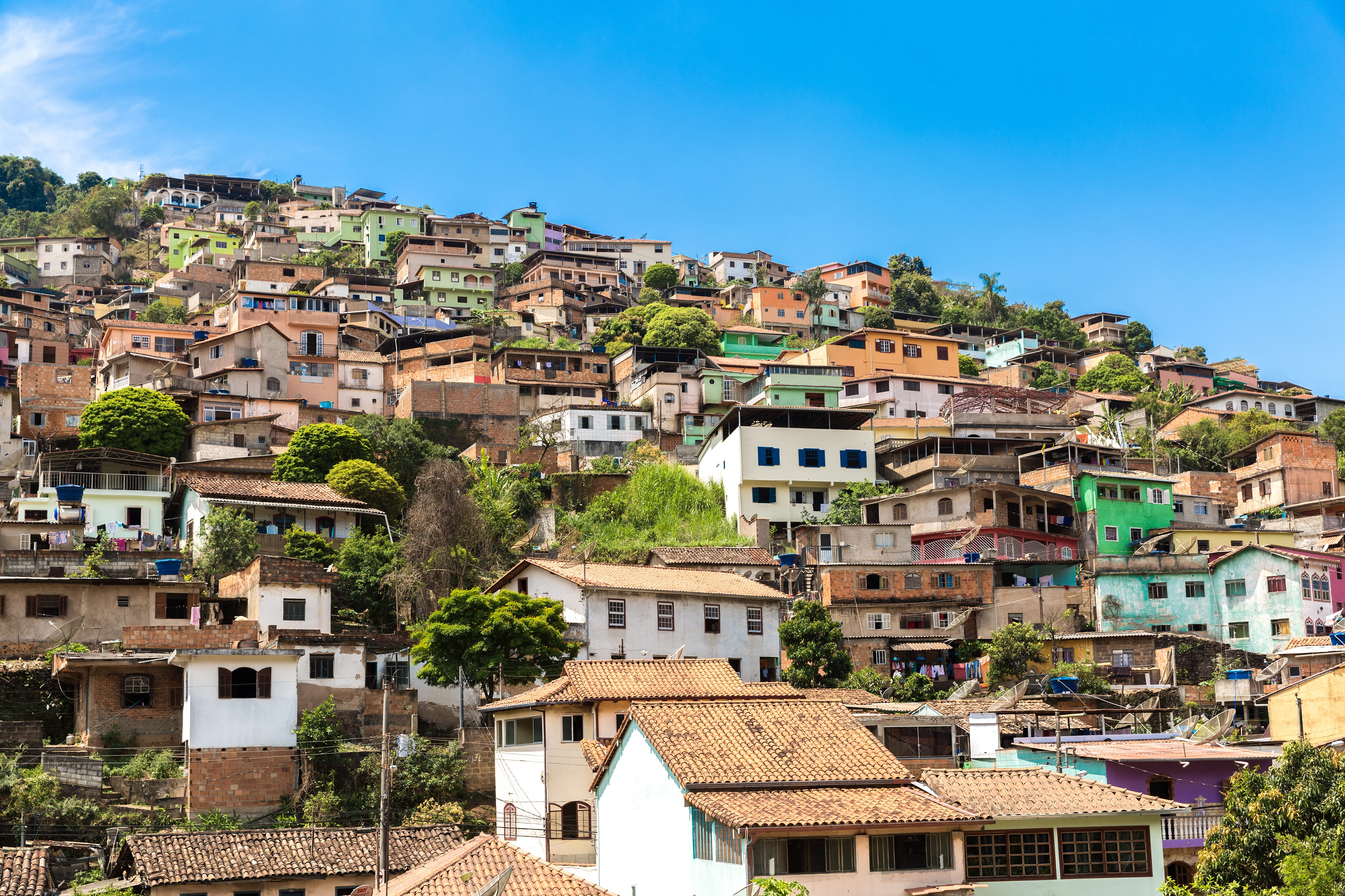 A very famous scenario in Brazil: the Favelas. The sky is blue and sunny. The neighbourhood is full of collors, but brown tones still prevails.
