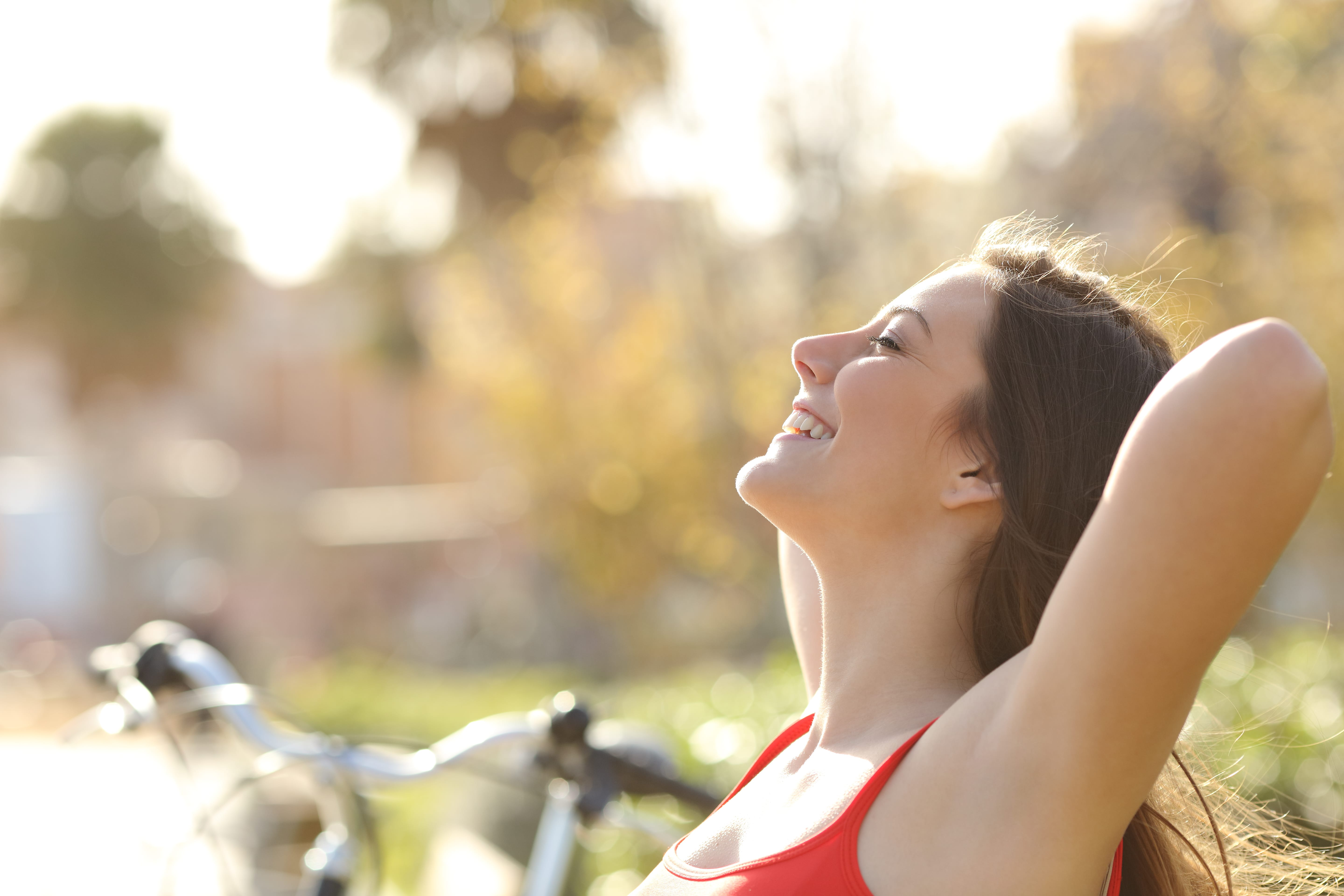 In a expression of freedom and happiness, a woman is smiling with both arms up. At the background, there is a blurred bicycle and a nature landscape.